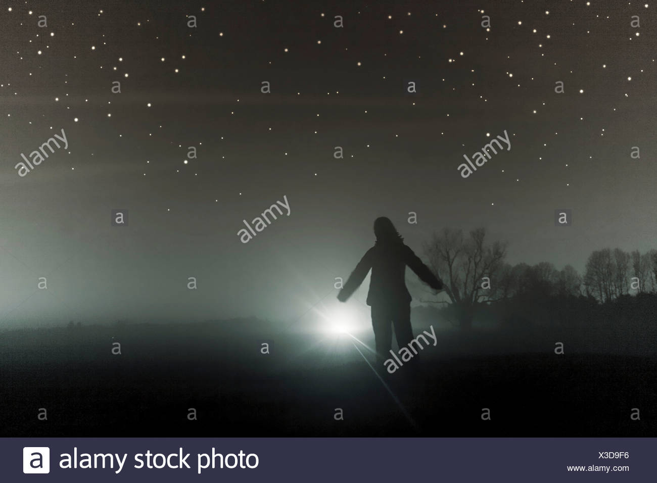 A silhouetted figure standing in a field with a bright light in the distance - Stock Image