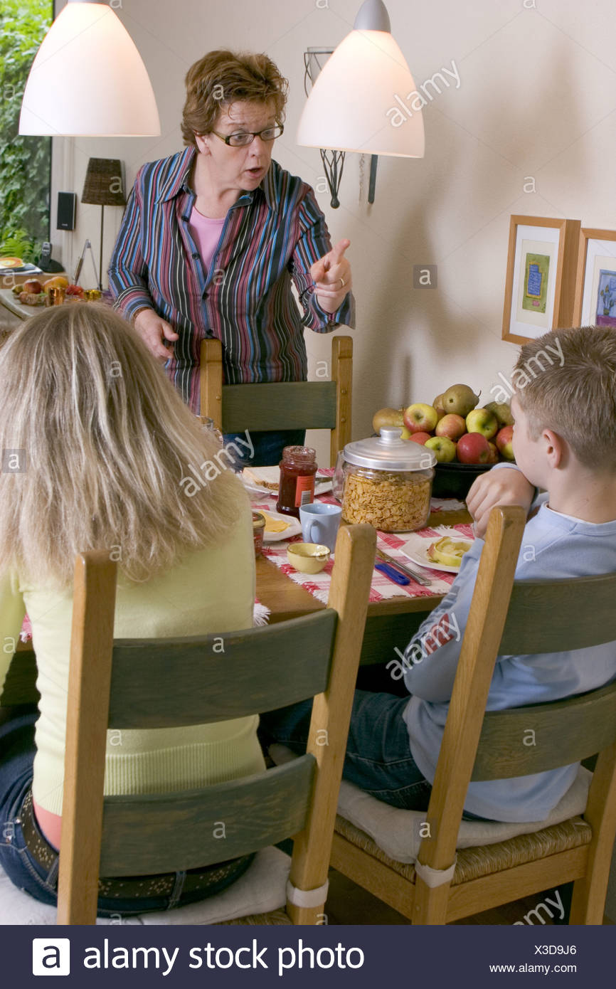 Verbal abuse: Demanding mother telling off her children at home at dining table and being an aggressive mom. SerieCVS417009 Stock Photo