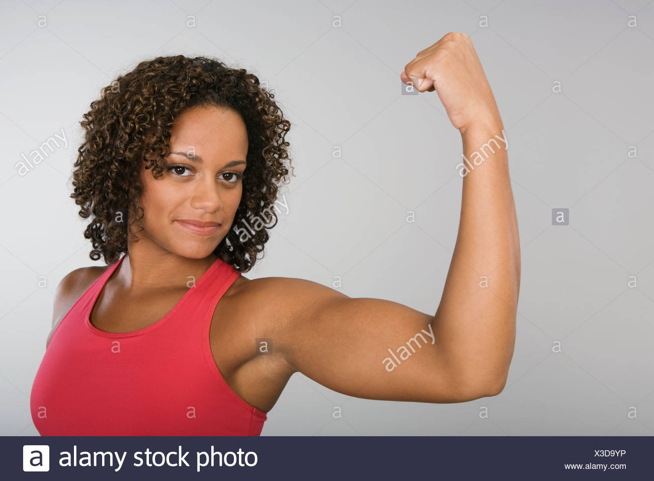 African woman flexing biceps - Stock Image