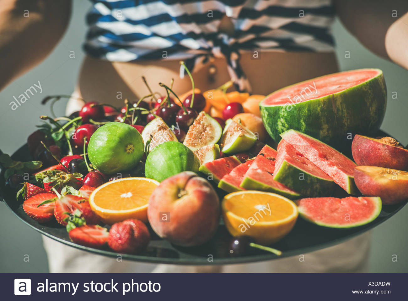 Summer healthy raw vegan clean eating breakfast in bed concept. Young girl wearing striped home shirt holding tray full of fresh seasonal fruit, selec - Stock Image
