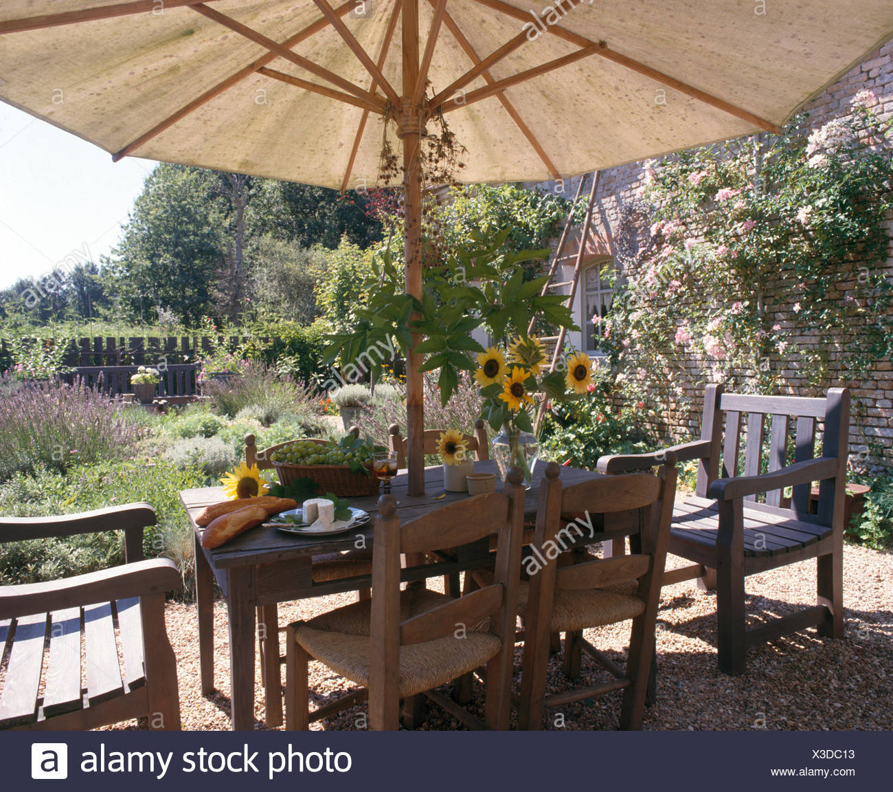 White umbrella above rustic ladder back chairs and wooden ...