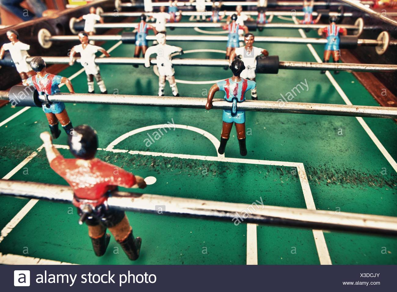 Table football in the bar, visible figures of toy mini football players wearing Real Madrid and Barcelona soccer team. - Stock Image