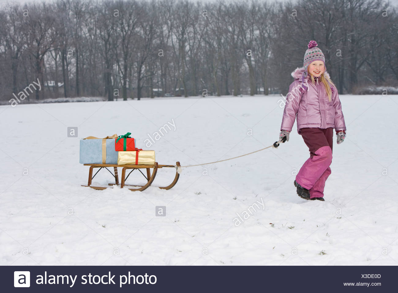 A young girl pulling a sled with presents on it - Stock Image