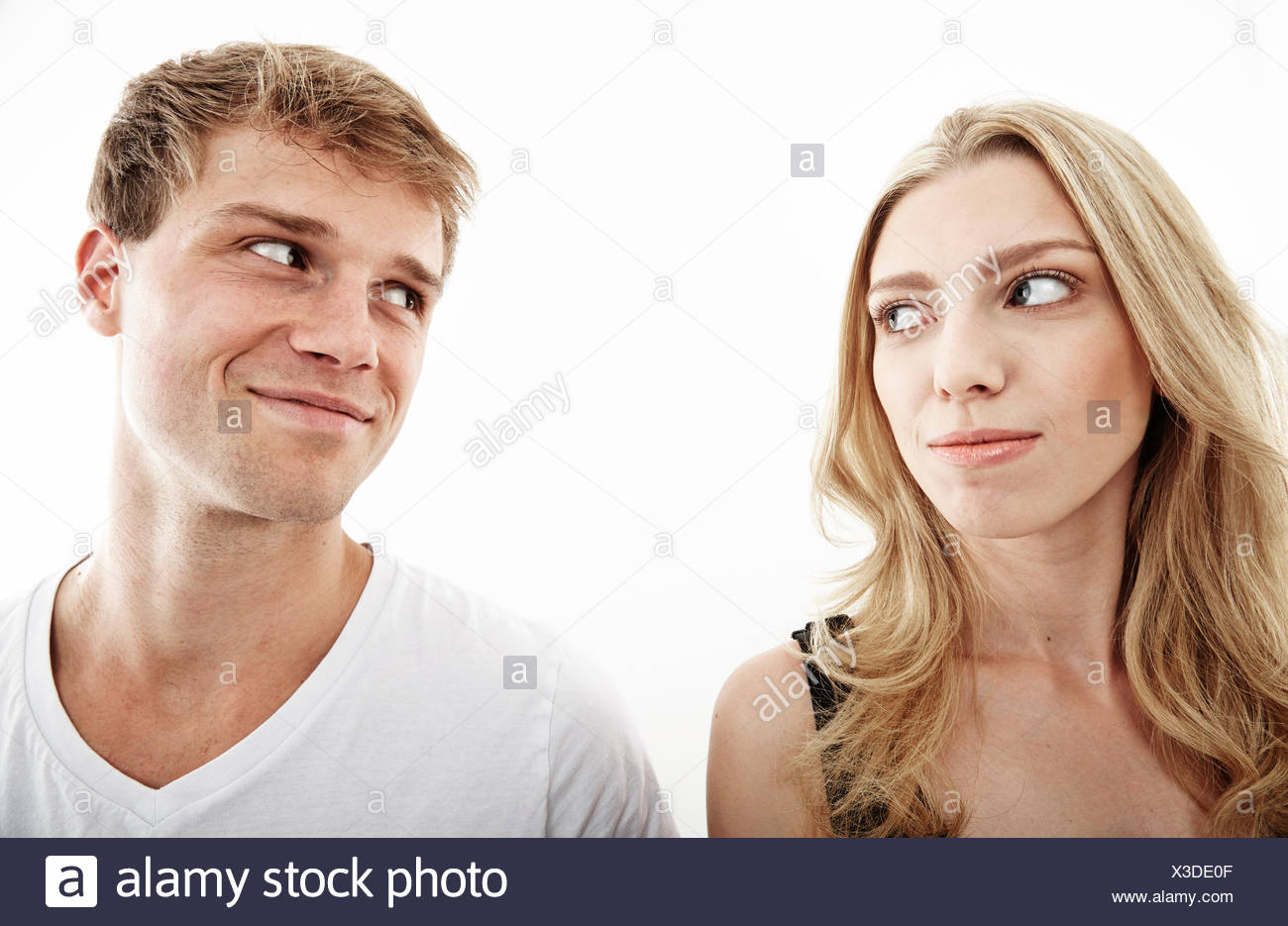 Studio portrait of young couple looking sideways at each other - Stock Image