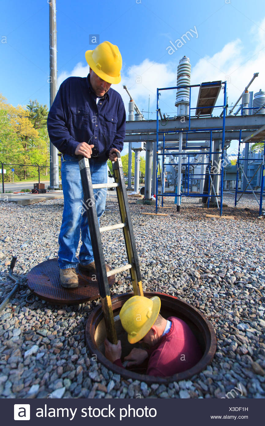 Power engineer entering manhole at a high voltage power distribution station, Braintree, Massachusetts, USA - Stock Image