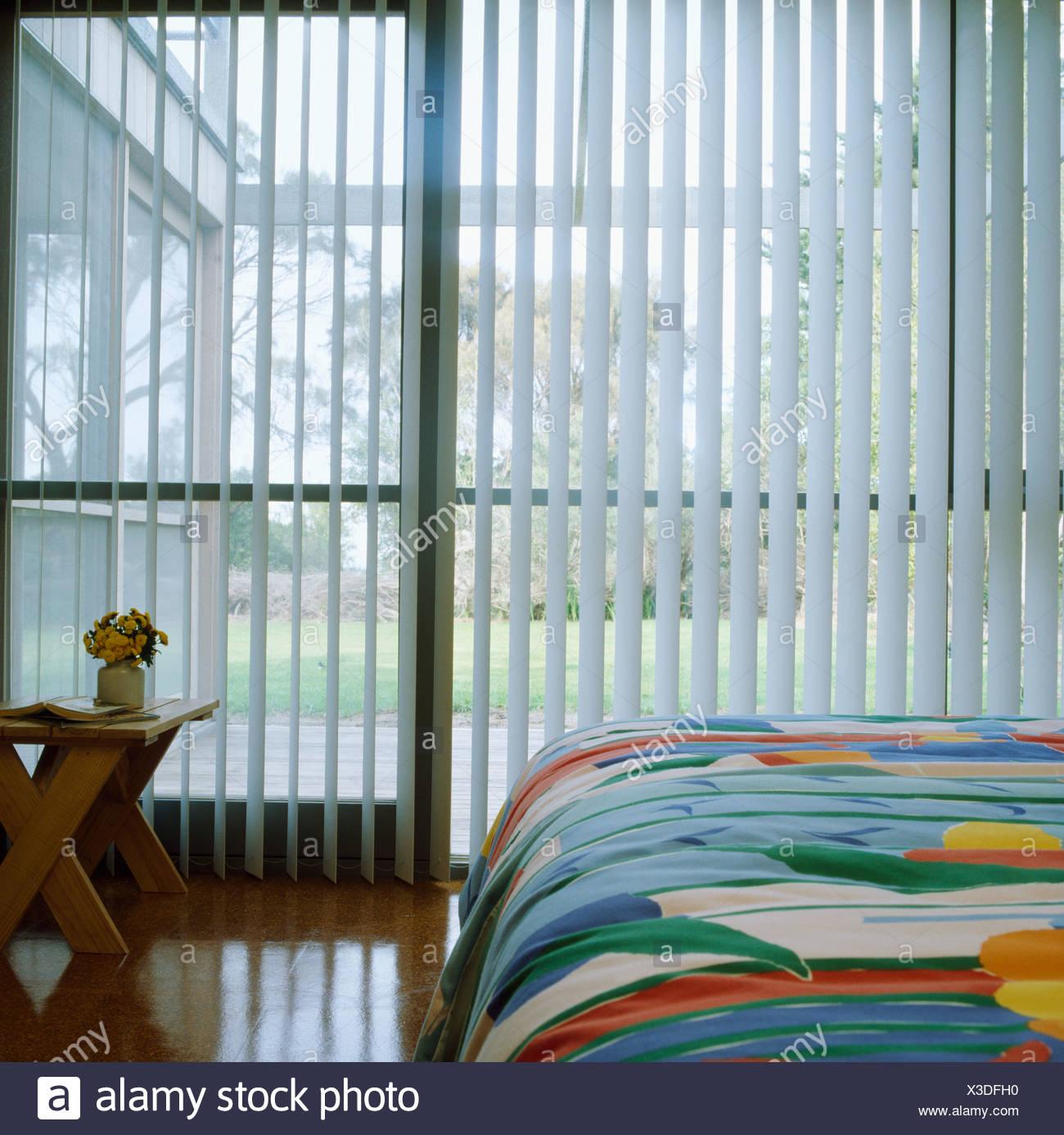 Multi Coloured Bedlinen On Bed In Front Of White Venetian Blinds