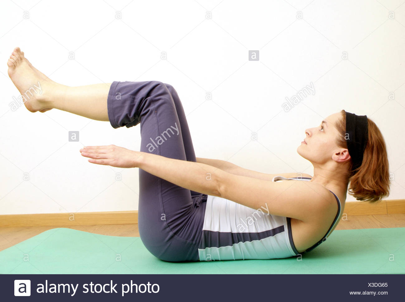 Woman does workout for tummy muscles - Stock Image