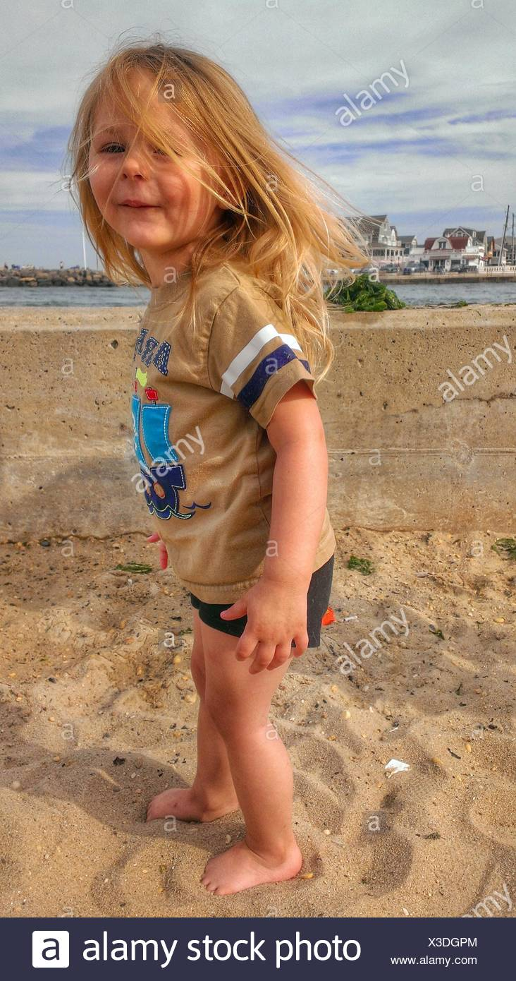 Full Length Portrait Of A Girl Standing On Beach - Stock Image