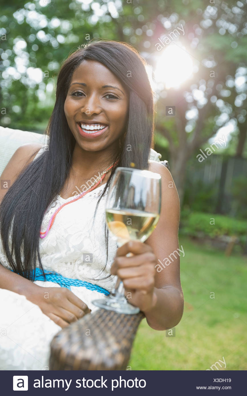 Portrait of happy woman with wineglass sitting in yard - Stock Image