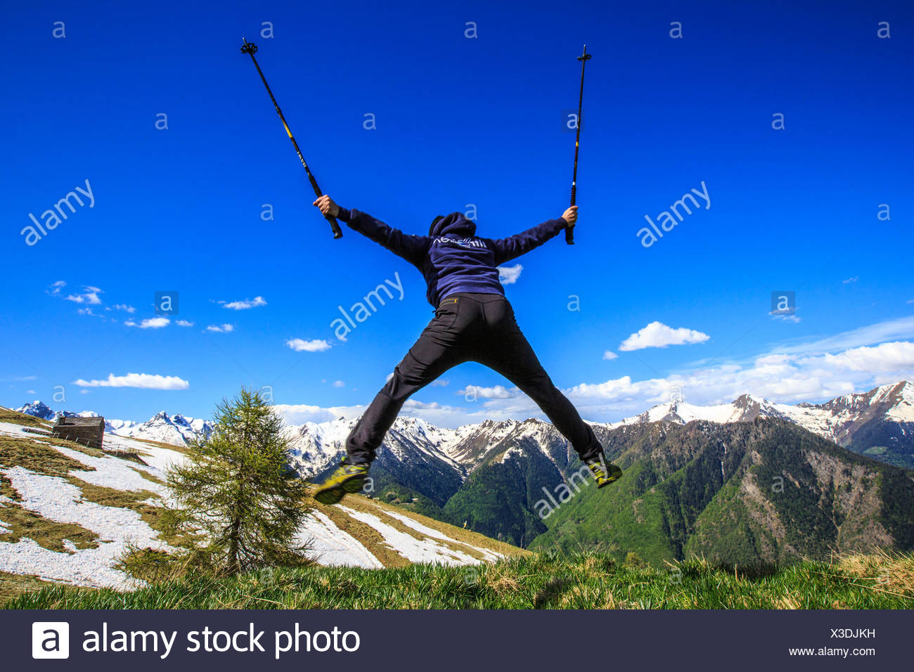 Hiker performs spectacular stunts on the slopes of Rosetta peak. Rasura. Valgerola. Valtellina. Lombardy. Italy. Europe Stock Photo