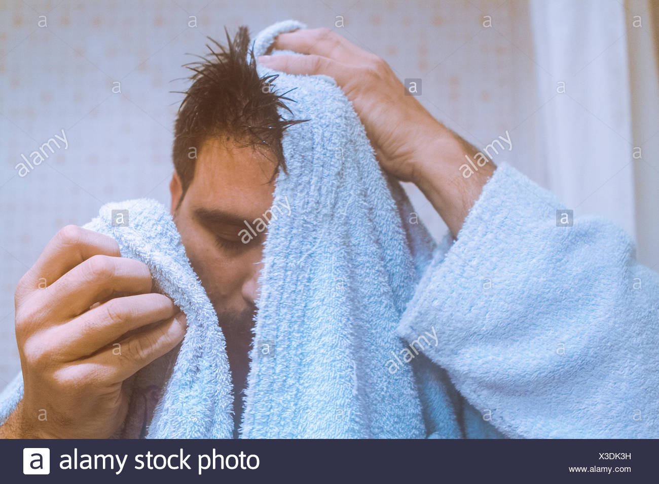 Man drying his face with towel - Stock Image