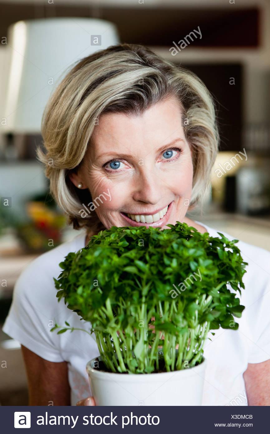 Senior Woman Holding Plant - Stock Image
