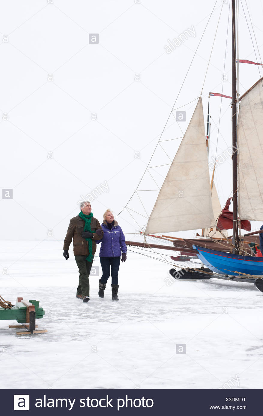 Senior couple walking on frozen lake near boats - Stock Image