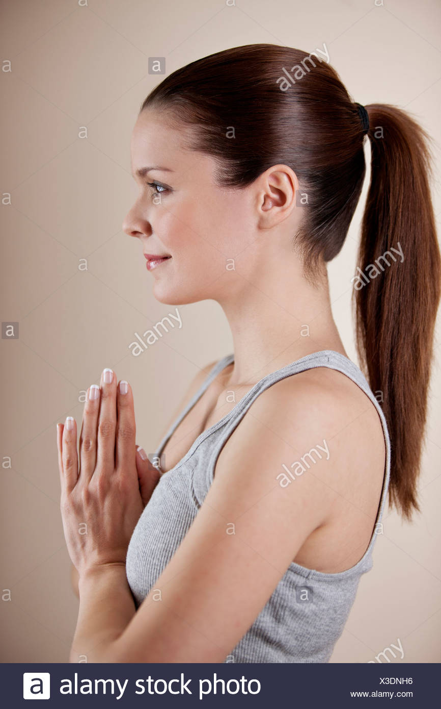 A young woman practicing yoga, hands in prayer position - Stock Image