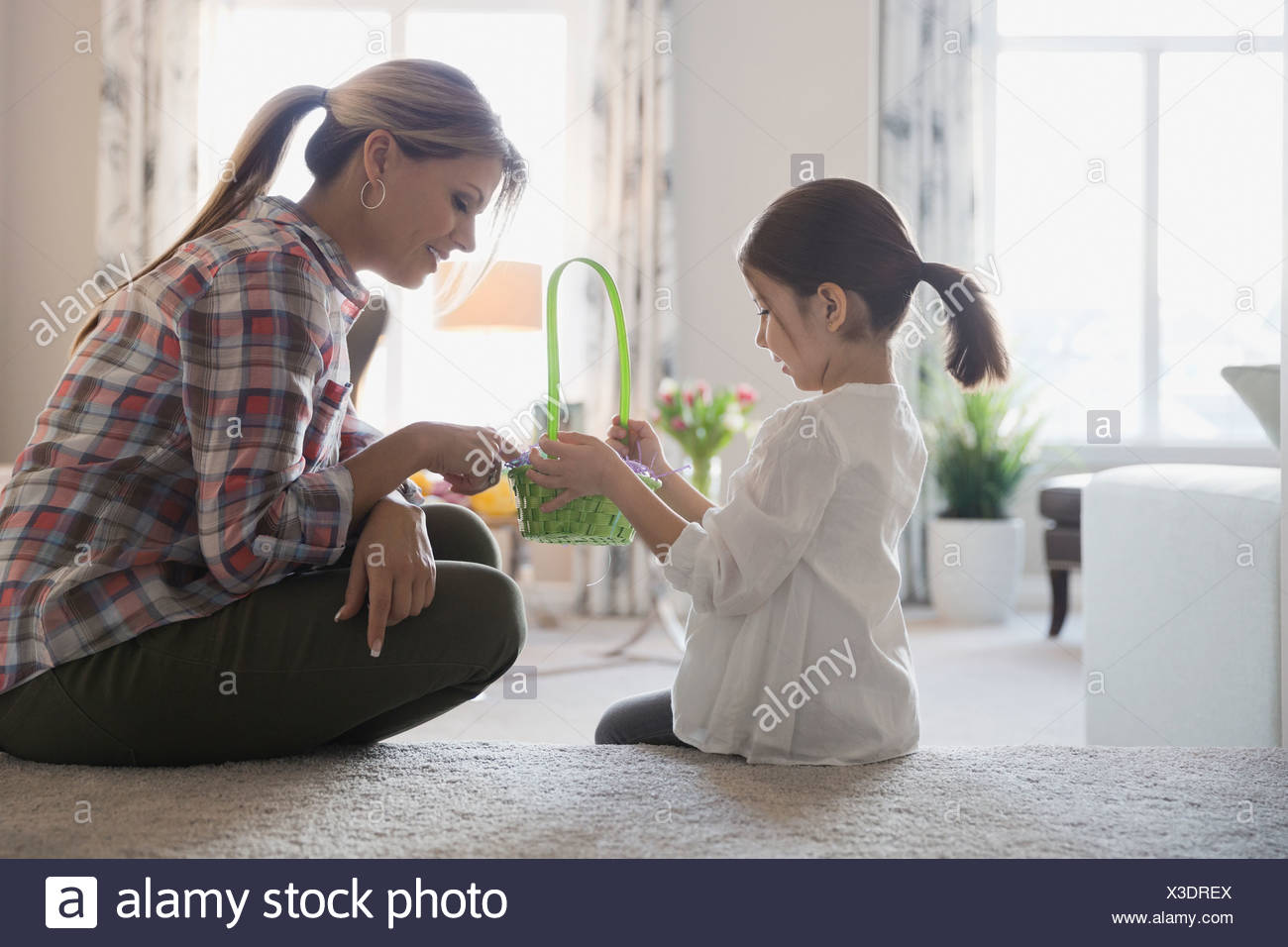 Mother and daughter counting Easter eggs at home - Stock Image