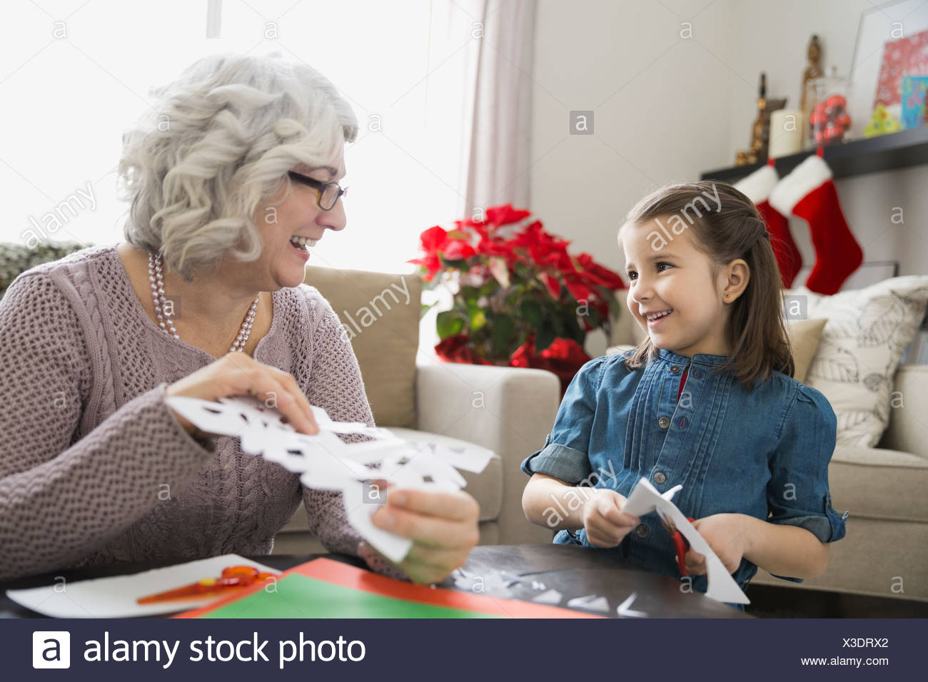 Grandmother and granddaughter making paper snowflakes - Stock Image