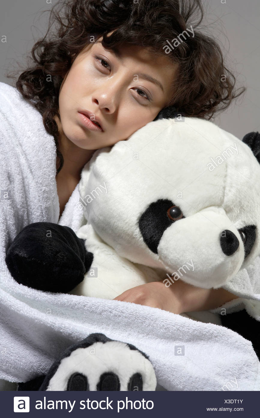 Young Woman In Bed Holding Panda Soft Toy - Stock Image
