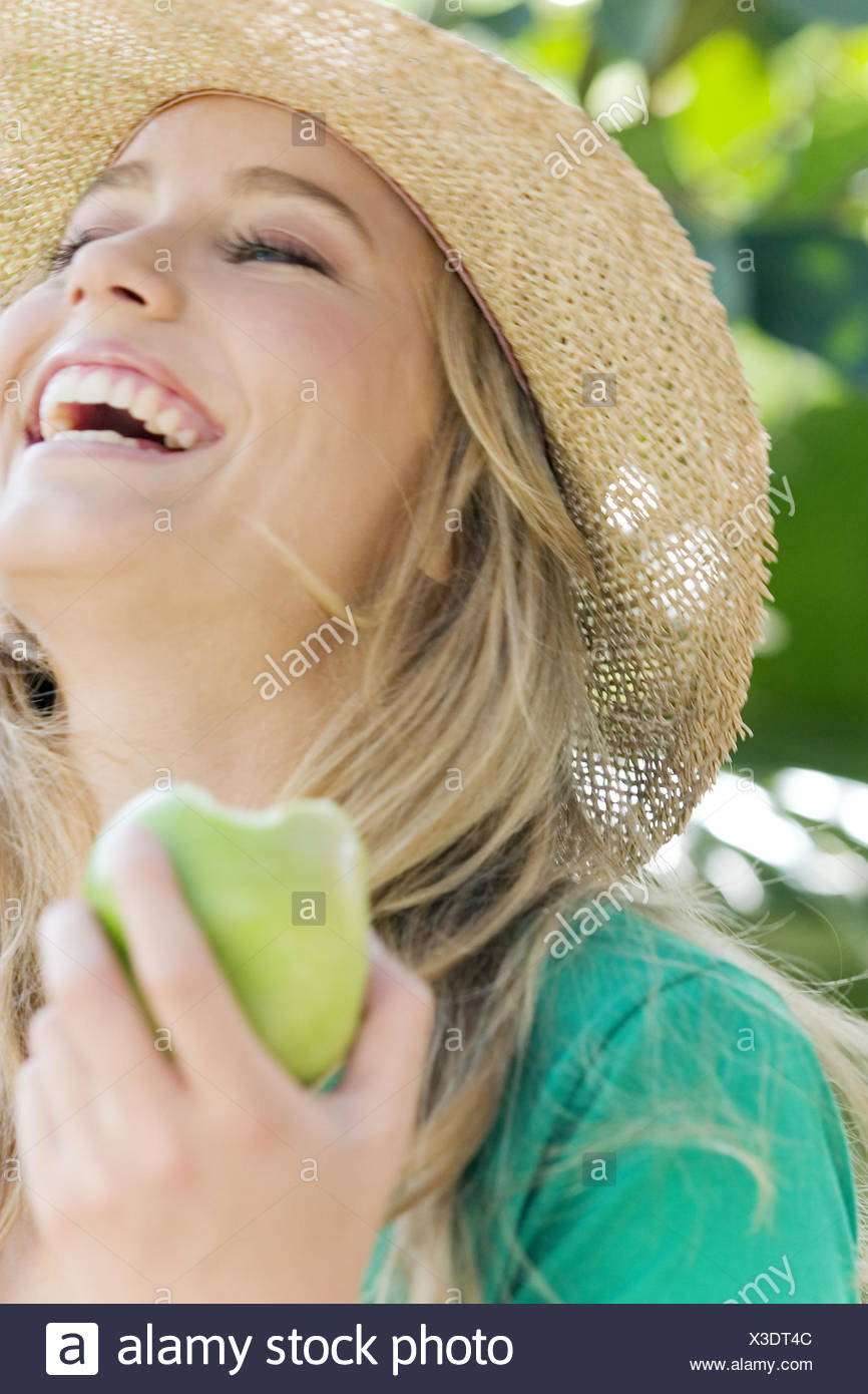Woman, young, laugh, apple, straw hat, garden, summer, - Stock Image