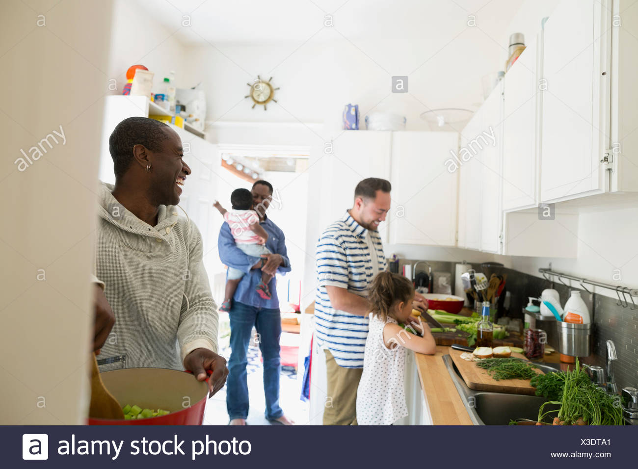 Fathers and children cooking in kitchen - Stock Image