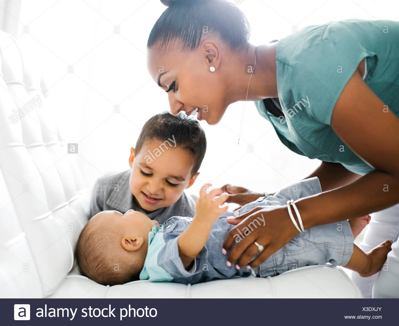 Mother with two sons (2-5 months, 2-3) on sofa - Stock Image