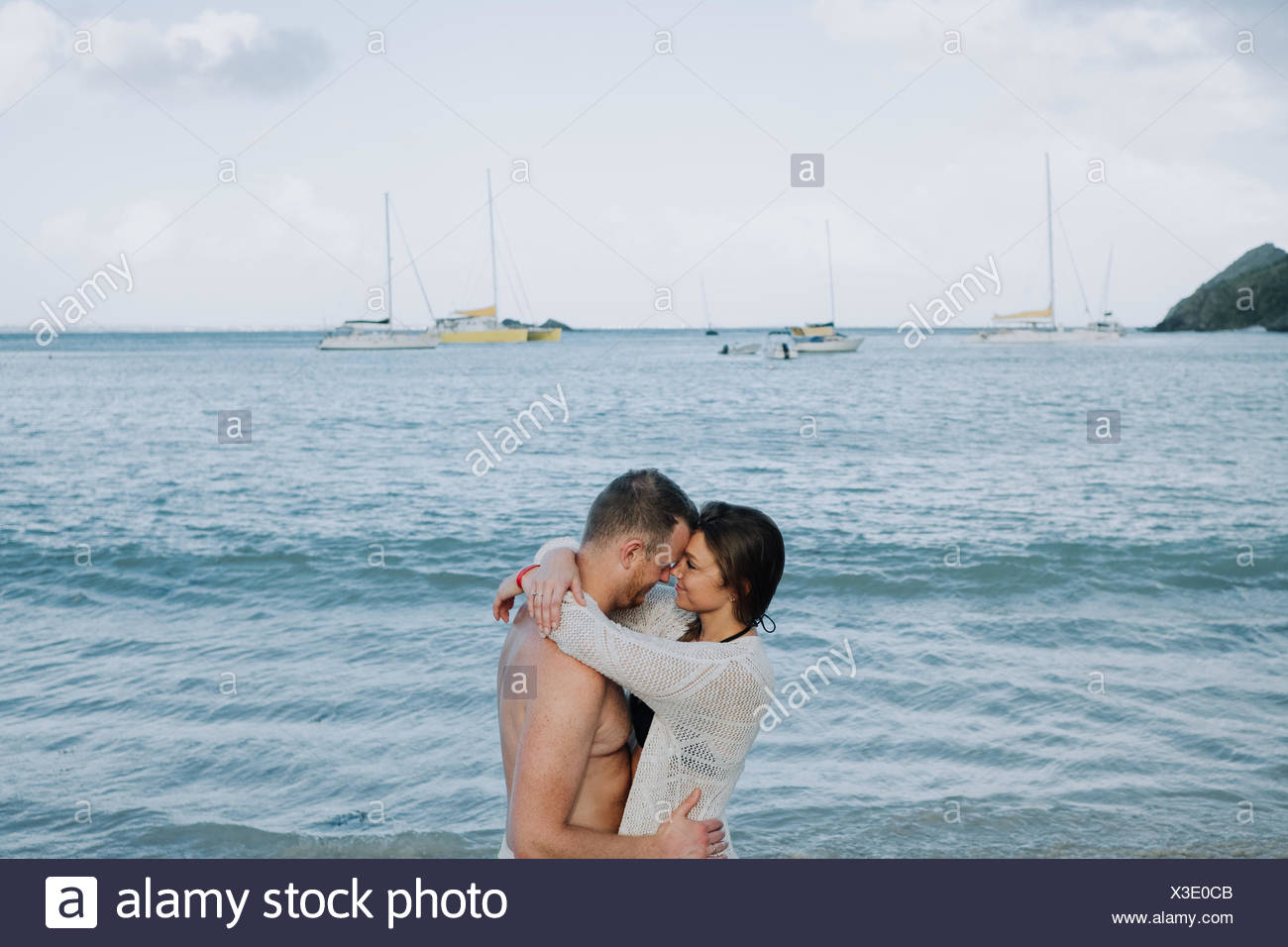 Couple standing by sea, hugging, face to face, Saint Martin, Caribbean - Stock Image