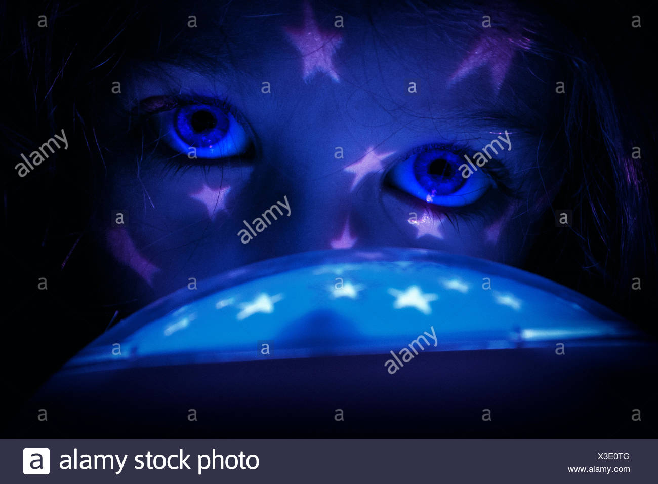 Girl with a star light reflecting in her face - Stock Image