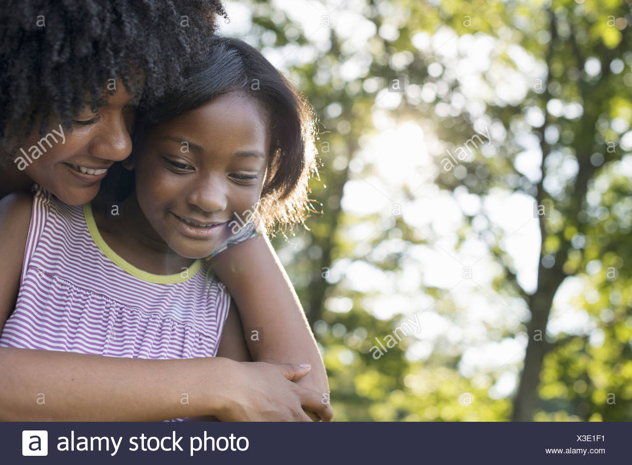 A young woman and a child hugging - Stock Image
