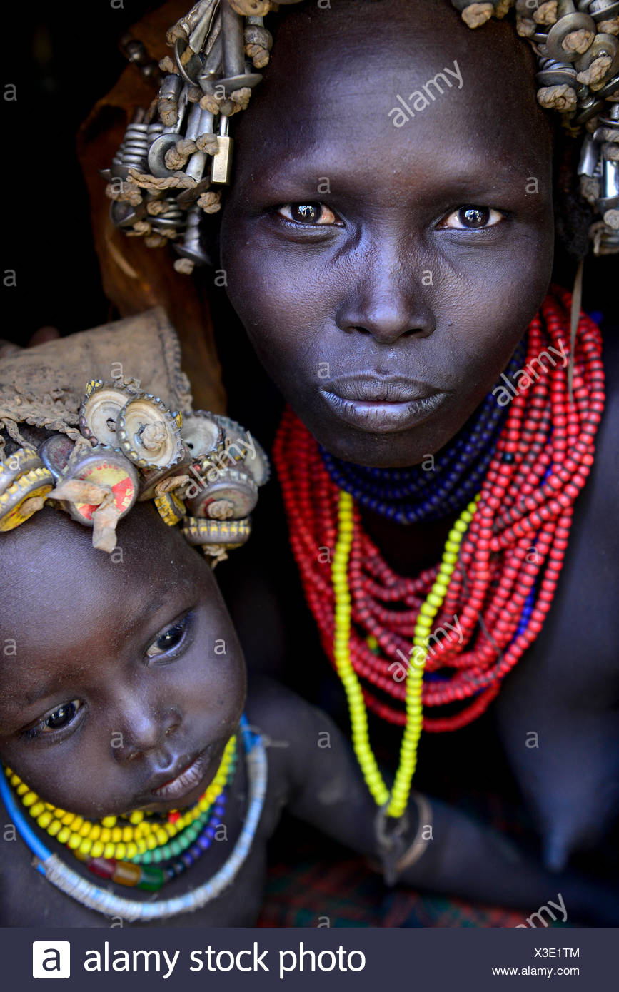 Dassanech woman with headdress of nuts and bolts, her son with headdress of bottle tops. Dassanech tribe, Lower Omo Valley. Ethi - Stock Image