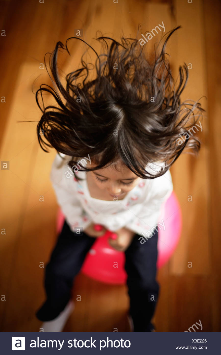 Girl aged five, bounces on pink moonhooper indoors - Stock Image