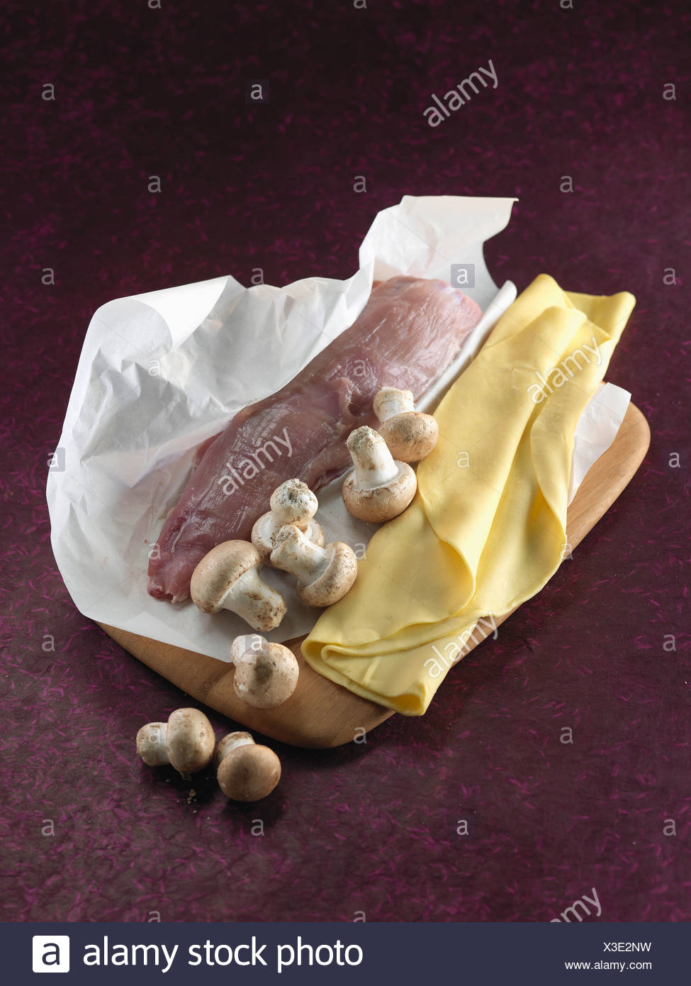 Pork fillet,uncooked flaky pastry and button mushrooms - Stock Image