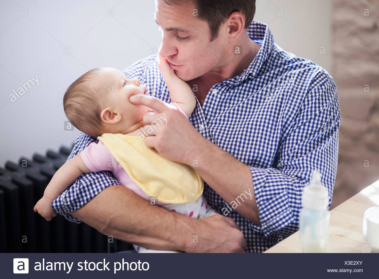 Father cradling baby daughter - Stock Image
