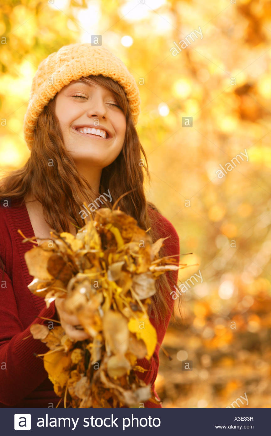 Young woman; Young woman holding autumn leaves - Stock Image