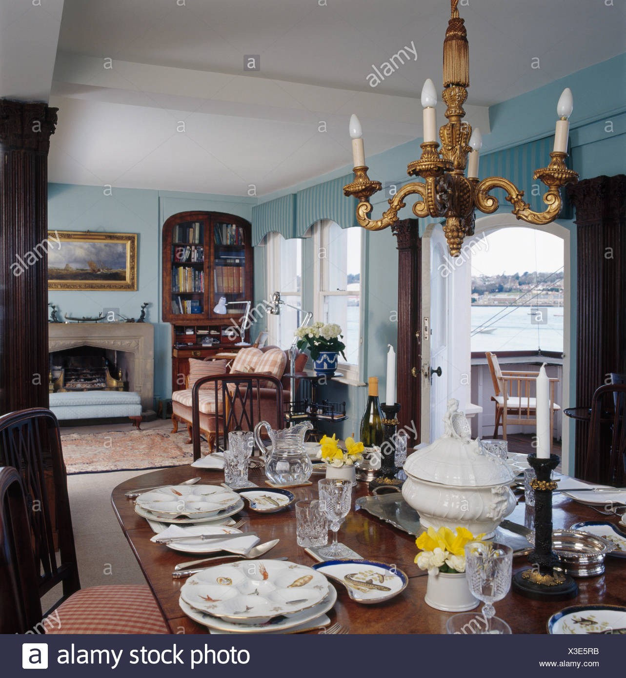 Picture of: Table Set For Lunch In Blue Coastal Dining Room With Gilt Chandelier Stock Photo Alamy
