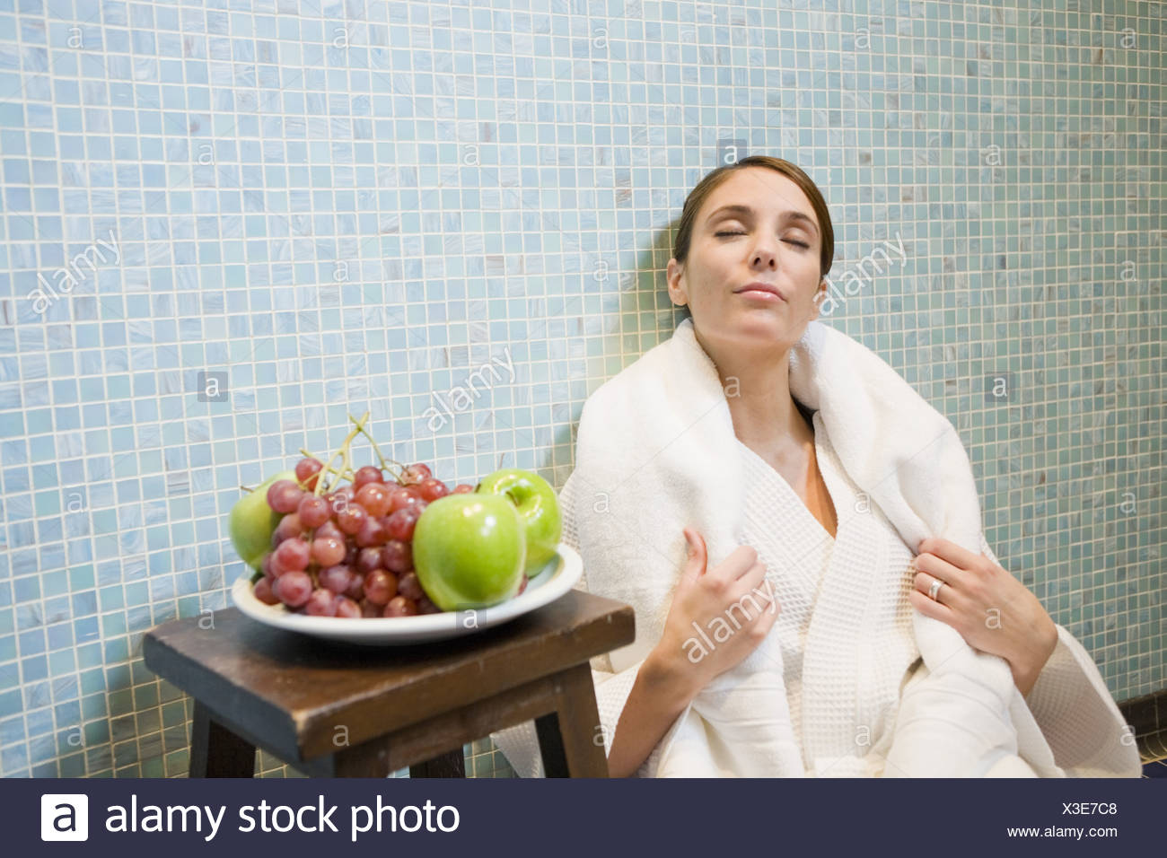 Woman in bathrobe leaning on tile wall - Stock Image