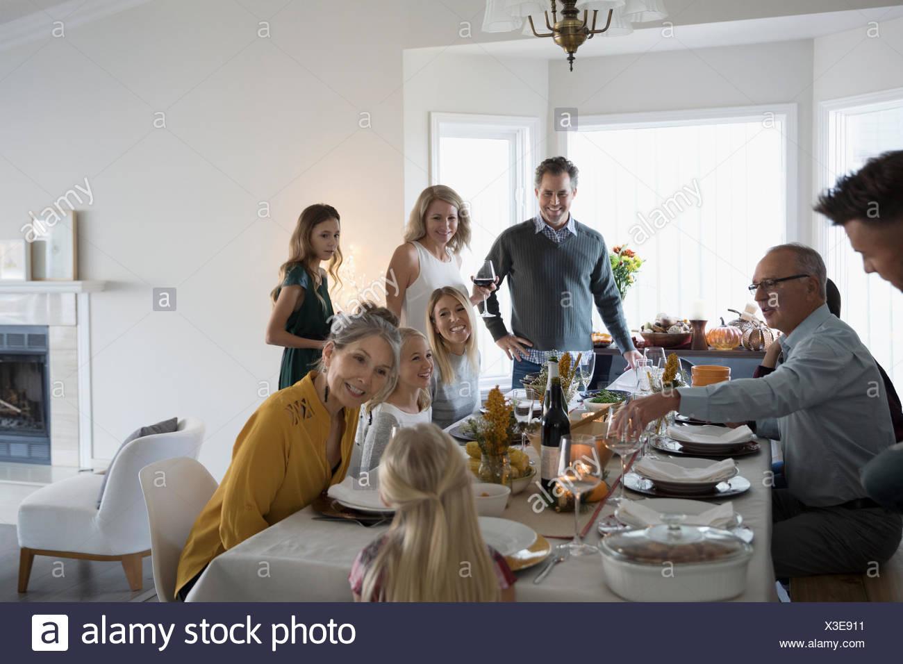 Multi-generation family enjoying Thanksgiving dinner at table - Stock Image