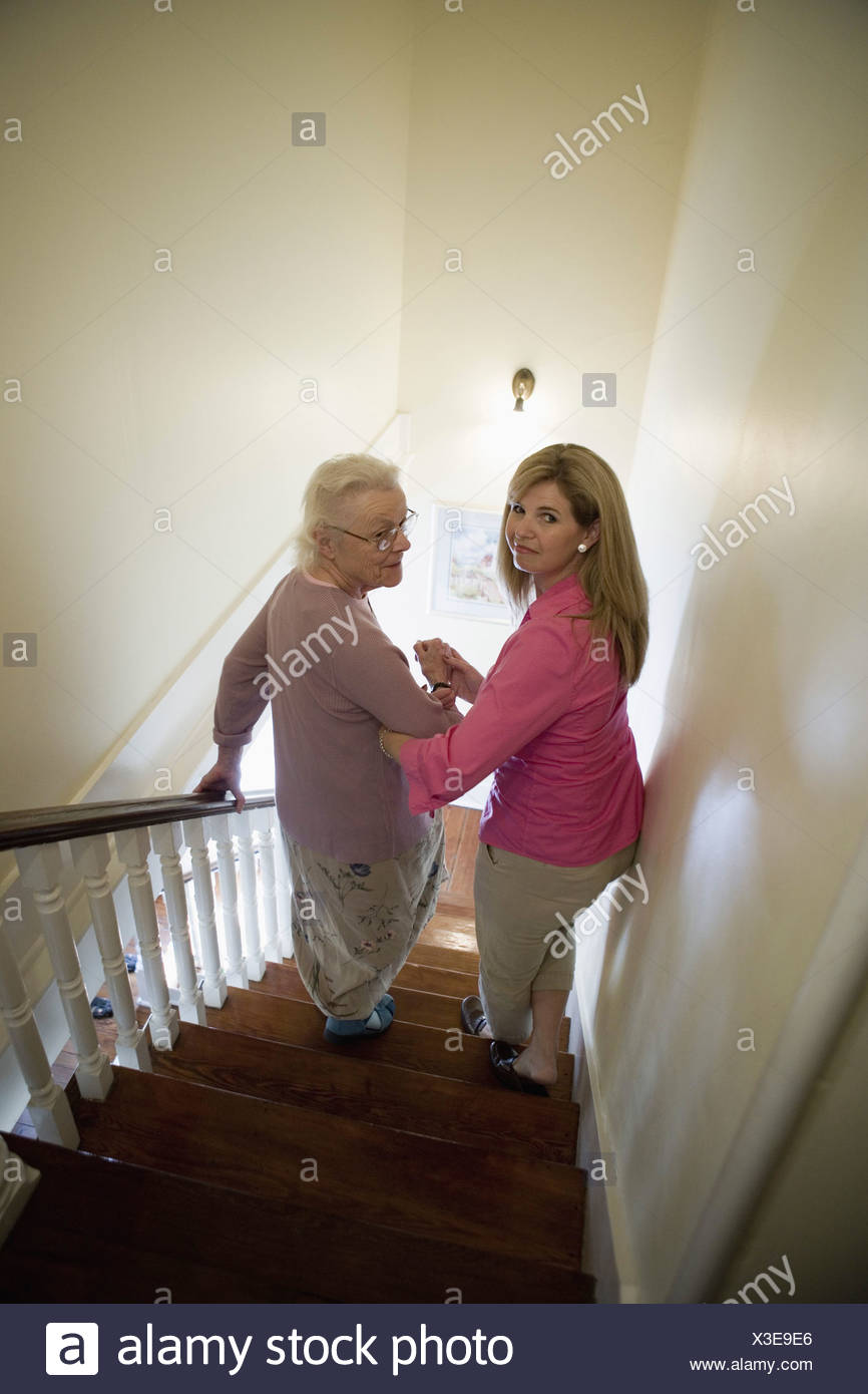 Woman supporting and helping senior woman down the stairs Stock Photo