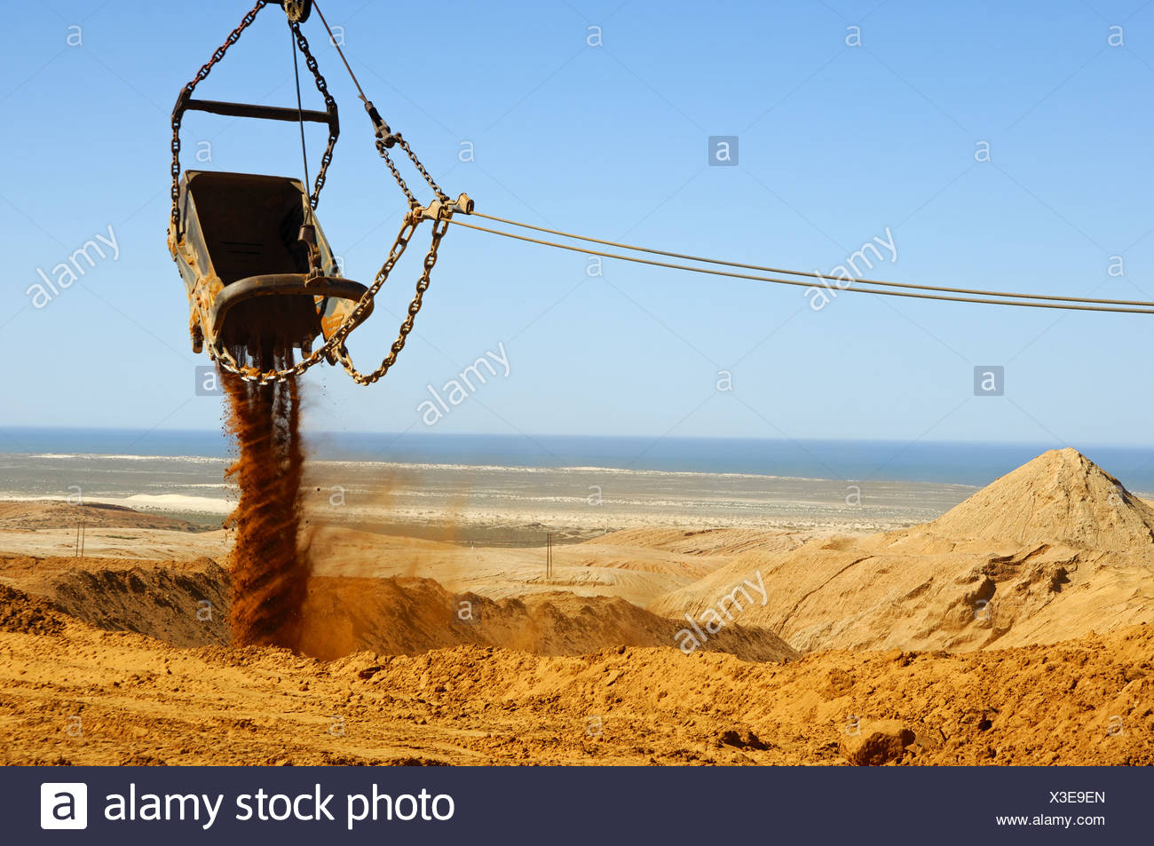 Bucket of a dragline excavator dumping earth - Stock Image