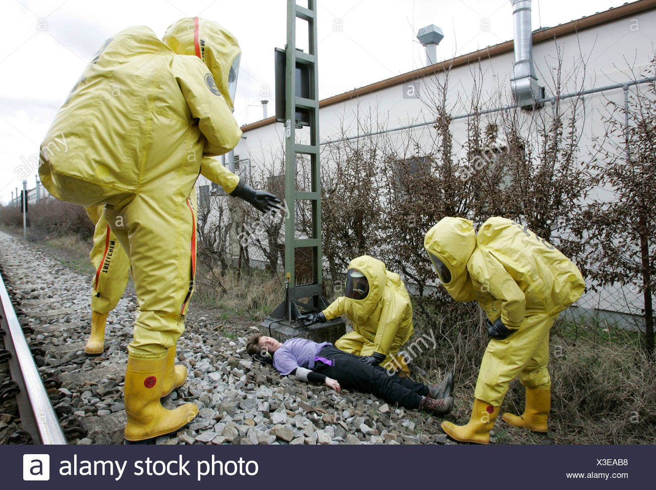 Firemen wearing hazmat suits rescuing actors during a disaster control drill, near Poing, Bavaria, Germany, Europe - Stock Image