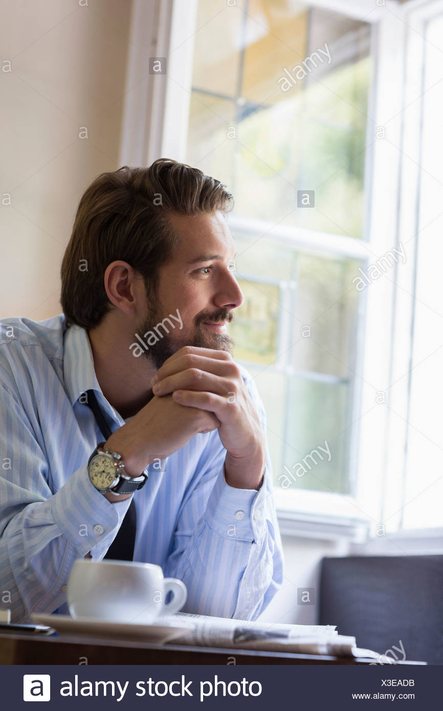 Portrait of man with hands clasped - Stock Image