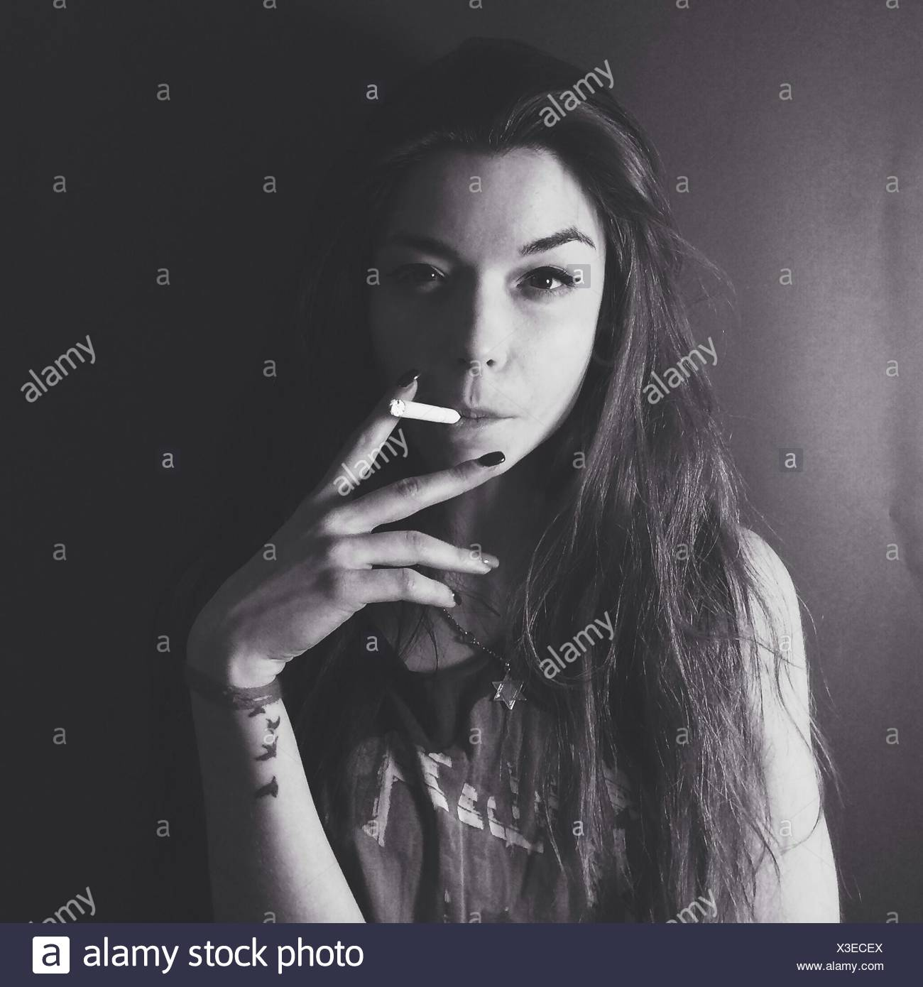 Portrait Of Young Woman Smoking Against Plain Background - Stock Image