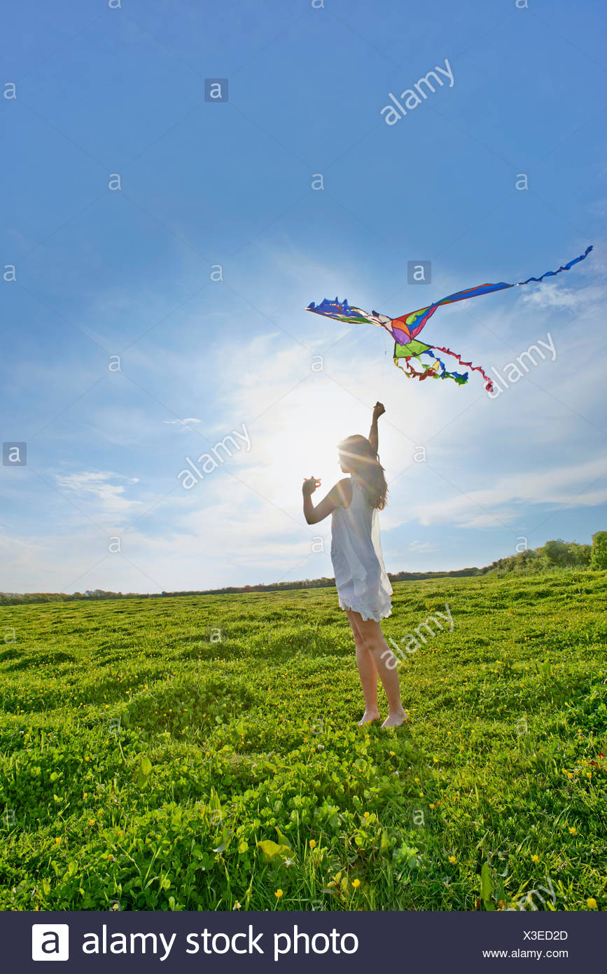 Young woman flying a kite in field - Stock Image
