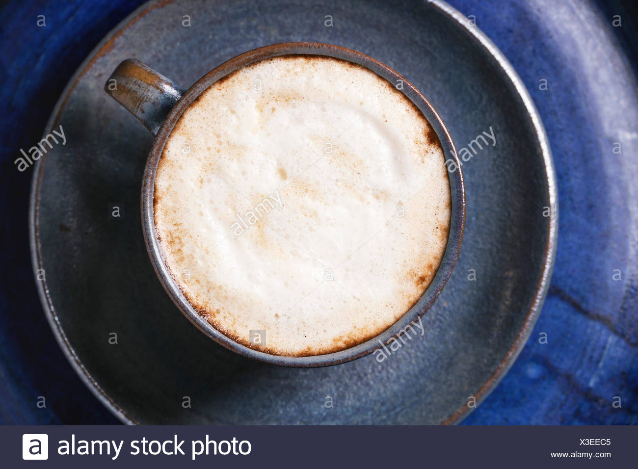 Blue ceramic cup of cappuccino over blue ceramic tray. Top view. - Stock Image