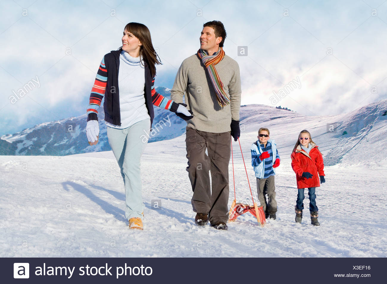 Family pulling sled in snow - Stock Image