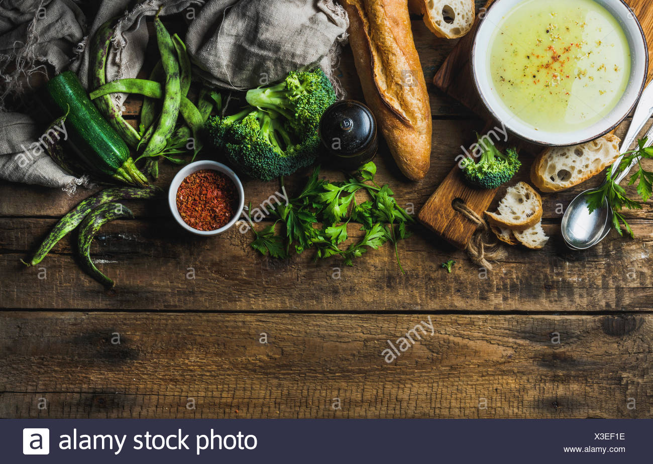Zucchini, broccoli and green beans cream soup in bowl with spices and fresh baguette over rustic wooden background. Top view, co - Stock Image