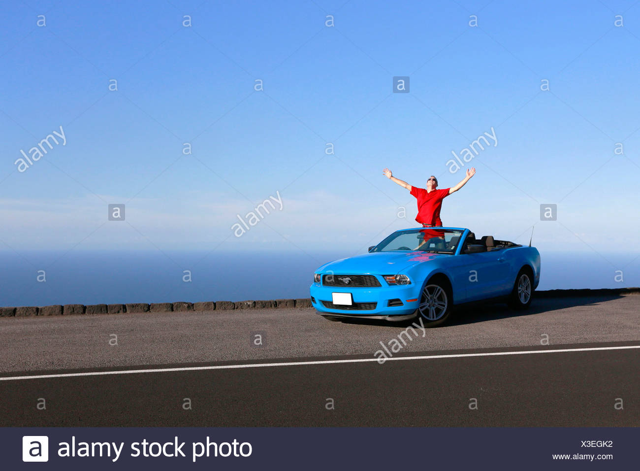 Happy man in a sky-blue Ford Mustang convertible by the sea, Big Island, Hawaii, USA - Stock Image