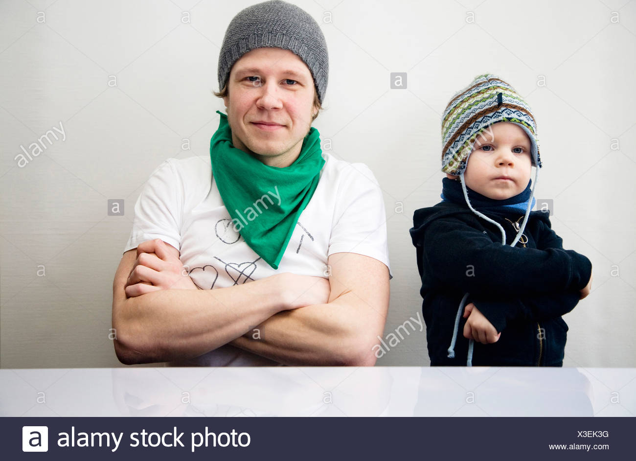 Father and son with folded arms sitting at a table, Germany - Stock Image