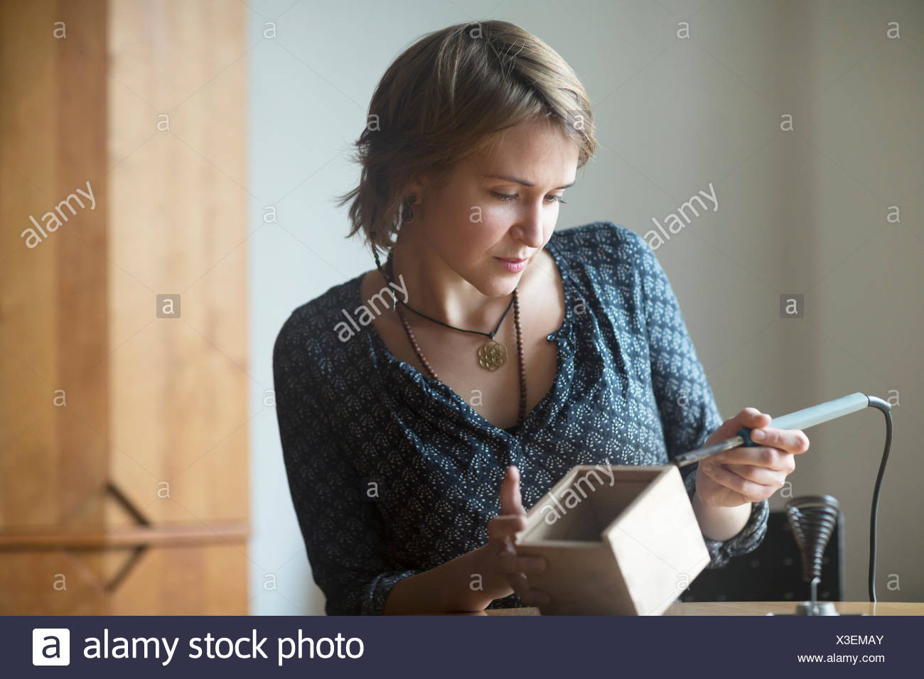 Young woman soldering something - Stock Image