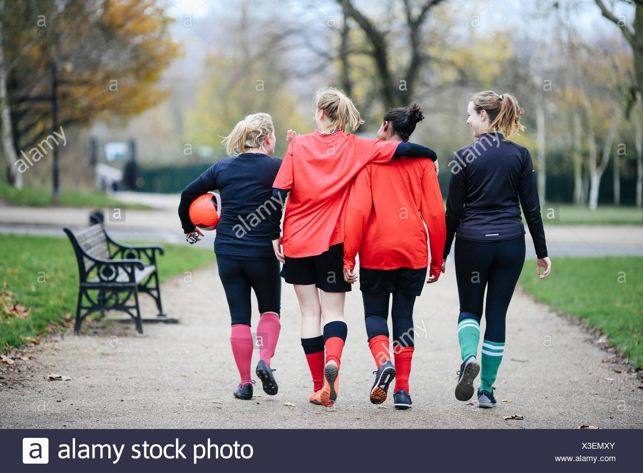 Rear view of female soccer players en route to play soccer in park Stock Photo