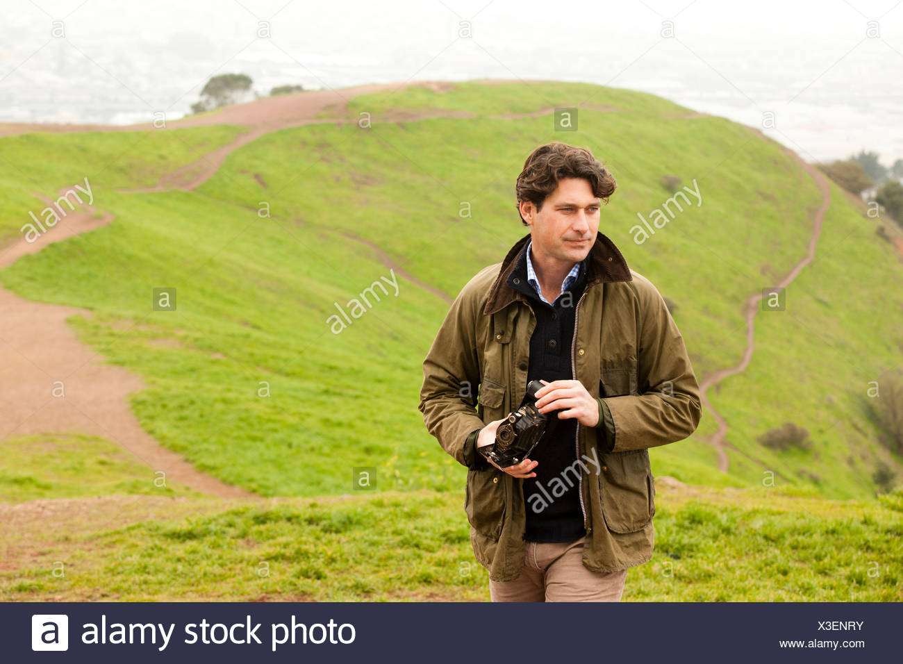 Mid adult man holding vintage camera in countryside, looking away - Stock Image