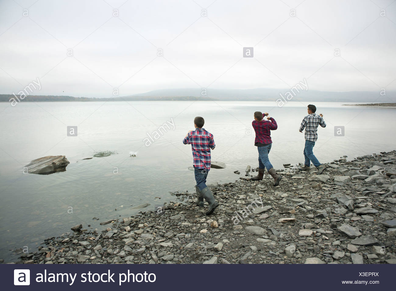 A day out at Ashokan lake Three boys on the shore throwing skimmers pebbles across the water - Stock Image